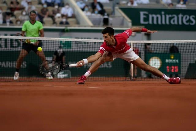 Novak Djokovic stretches for a backhand with Rafael Nadal watching
