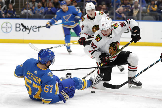 St. Louis Blues' David Perron (57) falls as he battles for a loose puck with Chicago Blackhawks' Adam Boqvist (27), of Sweden, during the second period of an NHL hockey game Saturday, Dec. 14, 2019, in St. Louis. (AP Photo/Jeff Roberson)