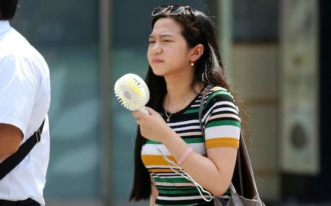 A woman holds a portable fan at a business district in Tokyo on Monday - Credit:  Koji Sasahara/AP