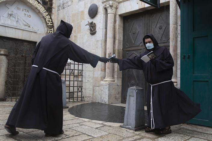 """Franciscan monks retrace the Via Dolorosa in Jerusalem's Old City after the traditional Good Friday procession was called off amid coronavirus fears. <span class=""""copyright"""">(Associated Press)</span>"""