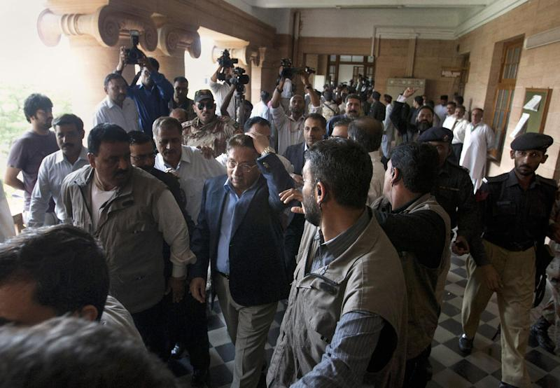 Former Pakistani President Pervez Musharraf, center, surrounded by  guards, holds his head after a shoe was thrown at him as he headed to court to face legal charges in Karachi, Pakistan on Friday, March 29, 2013. Musharraf, who first seized power in a military coup in 1999, returned to Pakistan last weekend after returning from self-imposed exile. (AP Photo/Shakil Adil)