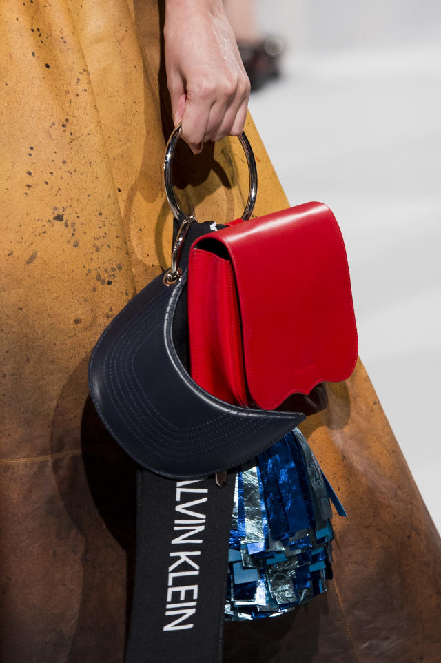 <p><i>Crimson bag with circular metal handle from the SS18 Calvin Klein collection. (Photo: ImaxTree) </i></p>