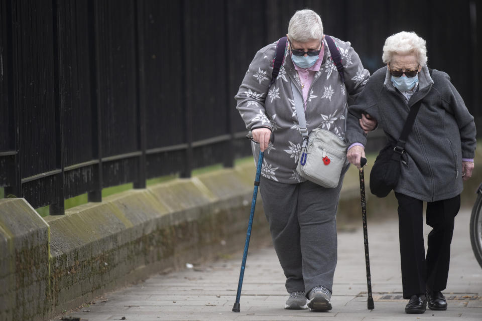 Two elderly women wearing protective face masks walk in Westminster, London as the UK continues in lockdown to help curb the spread of the coronavirus.