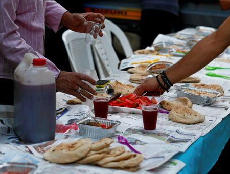 Egyptian Coptic Christians set up table with food and drinks to serve to their Muslim neighbours during Ramadan in Cairo