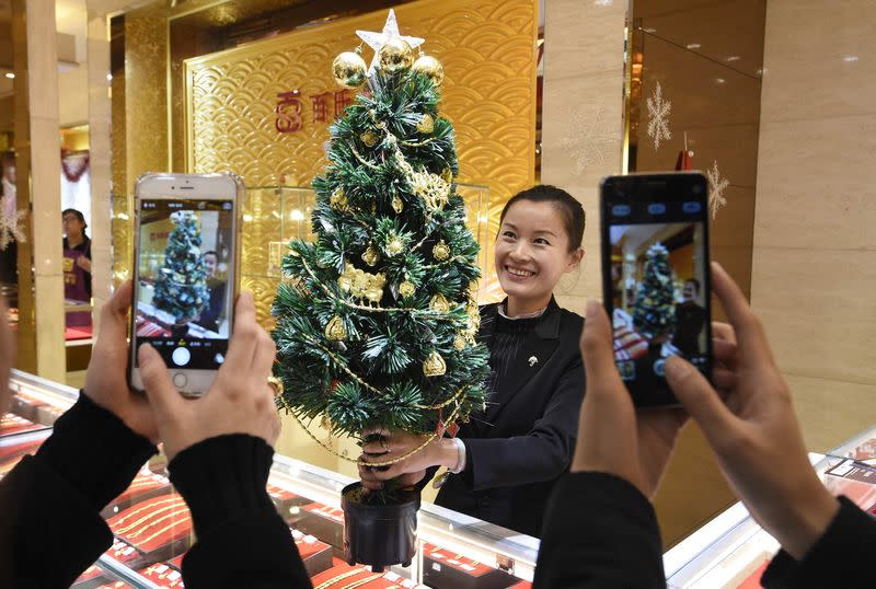 An employee poses for photographs with a Christmas tree decorated with gold accessories, as a promotional campaign of a gold store ahead of the Christmas, in Taiyuan