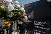 FILE PHOTO: People place a portrait of late Haitian President Jovenel Moise at a memorial outside the Presidential Palace