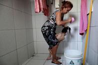 """Rosana Vieira Alves, 28, washes her two-year-old daughter Luana Vieira, who was born with microcephaly, at their house in Olinda, Brazil, August 6, 2018. Rosana has three daughters. """"It's hard to manage the girls. Some of them are jealous, but Luana needs more care. In time, they'll understand."""" Rosana does not have any family support and is overwhelmed by the cost of housing and Luana's medicines. She counts it a victory that she has managed to get a wheelchair for Luana, and worries about the four surgeries her daughter needs to correct problems with her eyes, her gut and the position of her hips and feet. The demands have taken Rosana to some dark places, and she confesses that she has considered suicide. But she still dreams of a better future, and hopes to get a degree in accounting or civil engineering. REUTERS/Ueslei Marcelino SEARCH """"ZIKA"""" FOR THIS STORY. SEARCH """"WIDER IMAGE"""" FOR ALL STORIES."""