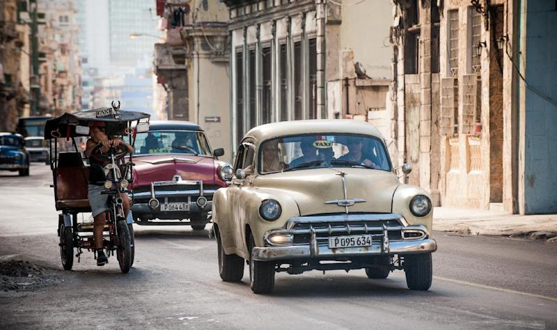 Old American cars are seen in a street of Havana, on December 19, 2014 (AFP Photo/Yamil Lage)