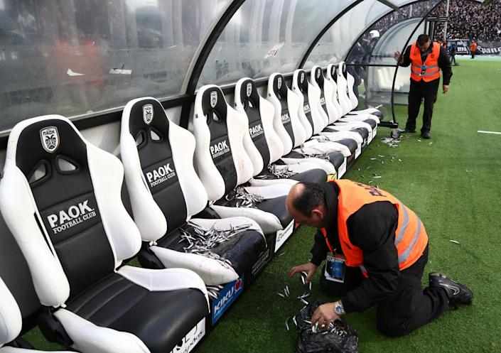 In this photo taken Wednesday, April 16, 2014 an employee of PAOK cleans Olympiakos' bench from fish before a semi-final of the Greek Cup in the northern port city of Thessaloniki. Police in Thessaloniki have arrested a PAOK fan accused of dumping a crate of fish on the visiting Olympiakos bench, in a jibe that delayed a tense Greek cup semi-final for more than an hour. Another six PAOK supporters were arrested during clashes with police before and after Thursday's match, which PAOK won 1-0 to advance on aggregate. The game was repeatedly halted by on-turf brawls, resulting in three red cards, while PAOK fans in the stands lit thousands of flares, and several were thrown on the pitch. (AP Photo/InTime Sports, Yorgos Matthaios) GREECE OUT