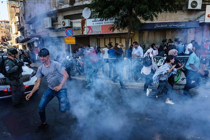 Israeli security forces throw stun grenades to disperse a crowd gathered for a news conference.
