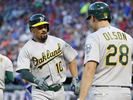 Oakland Athletics' Marcus Semien (10) celebrates with Matt Olson (28) after Semien hit a solo home run during the fifth inning of the team's baseball game against the Texas Rangers in Arlington, Texas, Friday, June 7, 2019. (AP Photo/Tony Gutierrez)