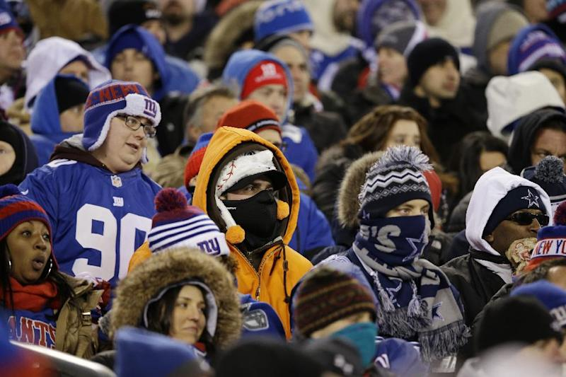 Fansare bundled up as they watch during the first half of an NFL football game between the Dallas Cowboys and the New York Giants Sunday, Nov. 24, 2013, in East Rutherford, N.J. (AP Photo/Seth Wenig)