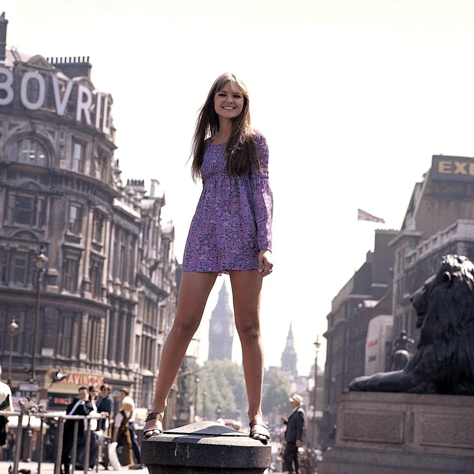 A female model stands on a plinth in Trafalgar Square, with the clock tower of the Palace Of Westminster visible through her legs, in a view of 1960s London. Circa 1965. (Photo by David Redfern/Redferns)  - Getty