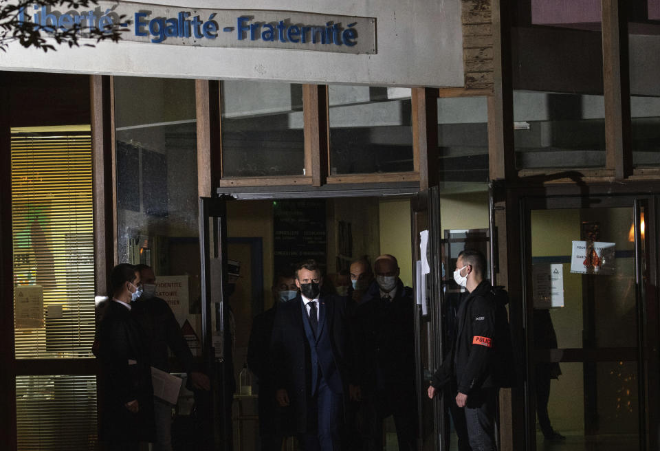 """French President Emmanuel Macron leaves, center, a high school Friday Oct.16, 2020 in Conflans Sainte-Honorine, northwest of Paris, after a history teacher who opened a discussion with high school students on caricatures of Islam's Prophet Muhammad was beheaded. French President Emmanuel Macron denounced what he called an """"Islamist terrorist attack"""" against a history teacher decapitated in a Paris suburb Friday, urging the nation to stand united against extremism. (Abdulmonam Eassa, Pool via AP)"""