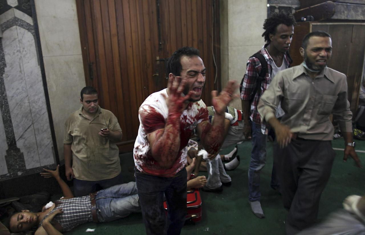 An Egyptian man covered with blood shouts inside the Al-Fath mosque that is being used as a makeshift hospital and is receiving casualties from clashes between security forces and supporters of Egypt's ousted President Mohammed Morsi in Ramses Square, downtown Cairo, Egypt, Friday, Aug. 16, 2013. Gunfire rang out over a main Cairo overpass and police fired tear gas as clashes broke out after tens of thousands of Muslim Brotherhood supporters took to the streets Friday across Egypt in defiance of a military-imposed state of emergency following the country's bloodshed earlier this week. (AP Photo/Khalil Hamra)