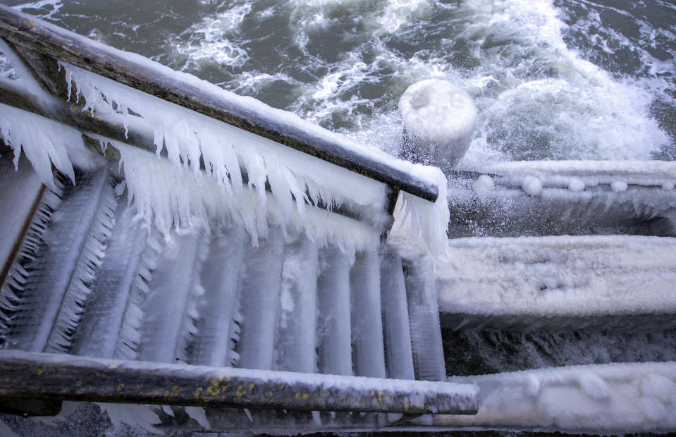 A thick layer of ice and icicles has formed over a jetty staircase at temperatures of around minus five degrees at the pier in Gohren, Germany, Sunday Feb. 7, 2021. Strong winds are causing snowdrifts and ice to form on the coastal region. (Jens B'ttner/dpa via AP)