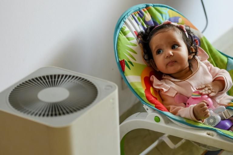 Six-month-old Ayesha rests near an air purifier at her home in Delhi