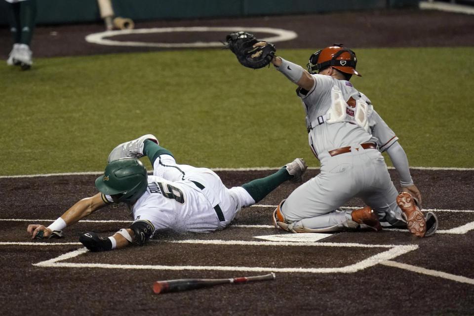 South Florida's Matt Ruiz (6) is tagged out by Texas catcher Silas Ardoin (4) as he tries to score during the fourth inning of an NCAA Super Regional college baseball game, Sunday, June 13, 2021, in Austin, Texas. (AP Photo/Eric Gay)