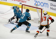 San Jose Sharks goaltender Aaron Dell (30) and Joakim Ryan (47) watch as the puck goes in the net as the Calgary Flames' Michael Frolik (67) skates by in the second period of an NHL hockey game in San Jose, Calif., Sunday, March 31, 2019. (AP Photo/Josie Lepe)