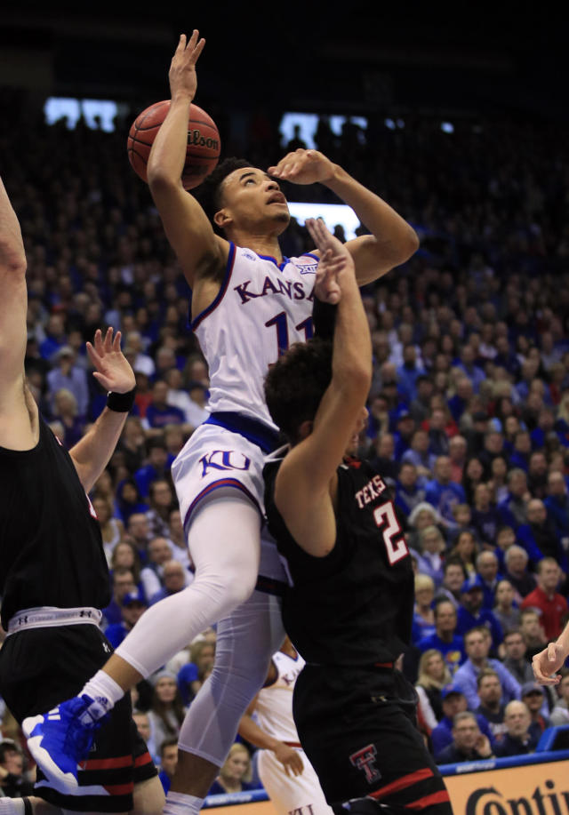 Kansas guard Devon Dotson (11) charges into Texas Tech guard Davide Moretti (25) during the first half of an NCAA college basketball game in Lawrence, Kan., Saturday, Feb. 2, 2019. (AP Photo/Orlin Wagner)
