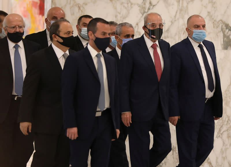 Lebanon's parliament speaker Nabih Berri wears a face mask as he walks at the presidential palace in Baabda