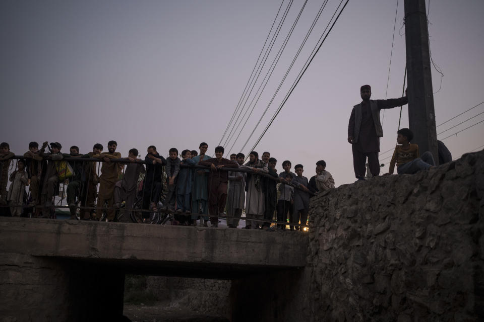 Afghans gather to watch Taliban fighters detaining drug users during a police operation in Kabul, Afghanistan, Friday, Oct. 1, 2021. The Taliban are shifting from being warriors to an urban police force. (AP Photo/Felipe Dana)