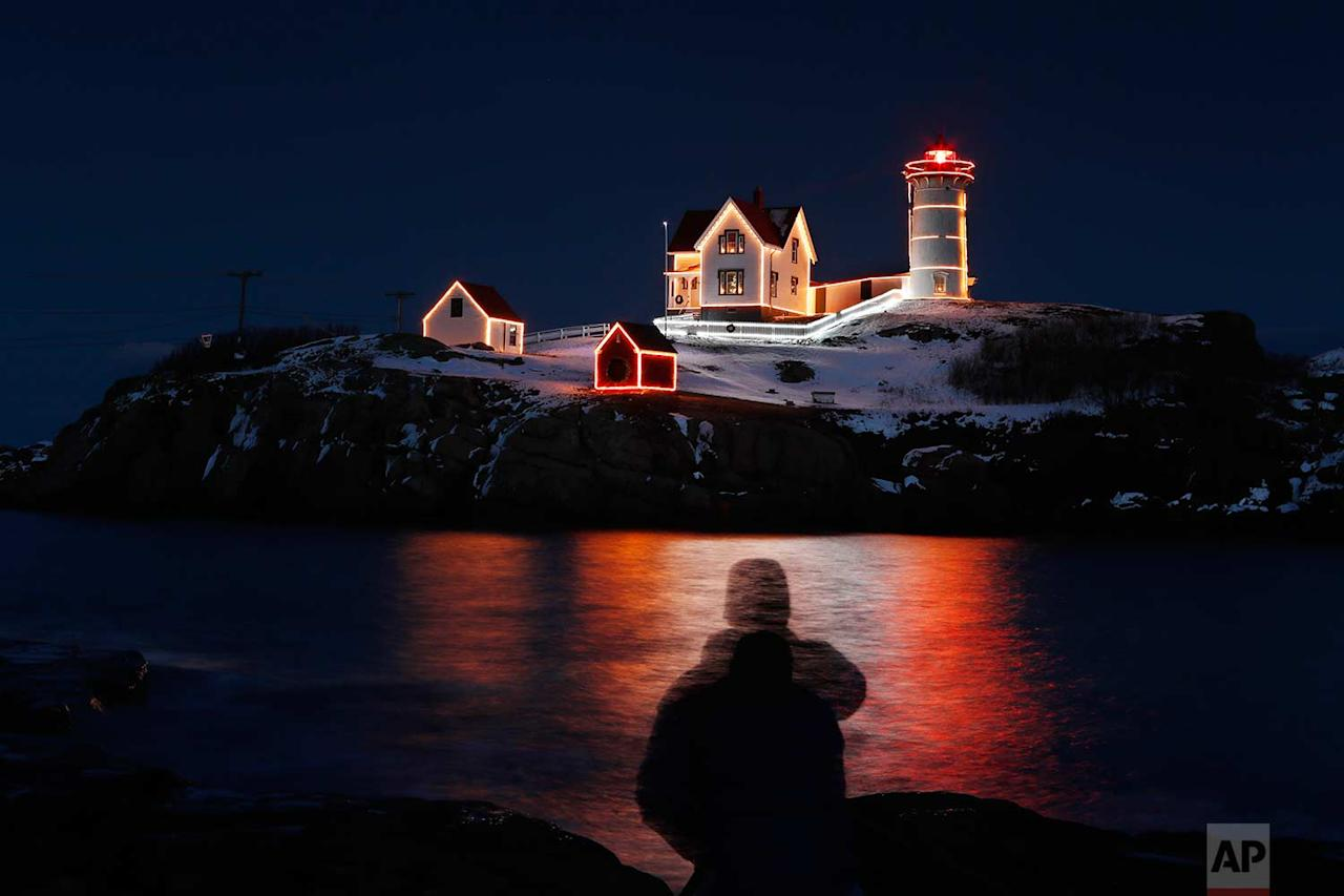 <p>In this long exposure shot, holiday lights reflect in the waters off Nubble Light, silhouetting photographer Michael Blanchette of Bedford, N.H in York, Maine. (AP Photo/Robert F. Bukaty) </p>