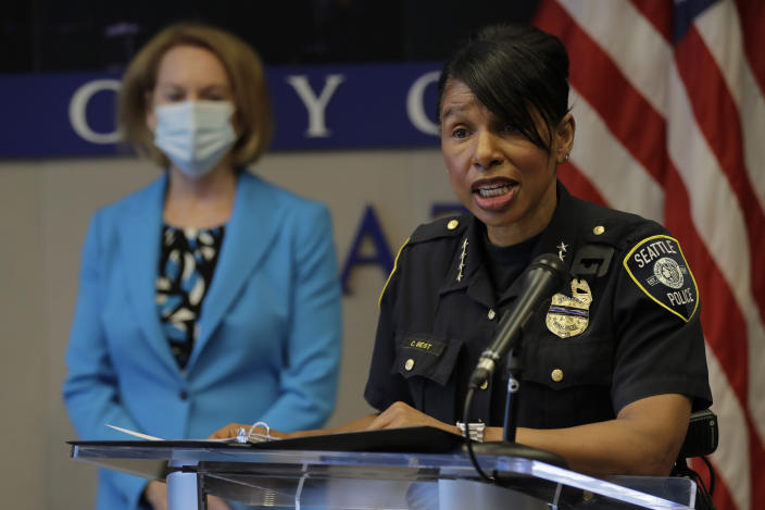 Seattle Police Chief Carmen Best, right, speaks, Monday, July 13, 2020, during a news conference at City Hall in Seattle. Best and Seattle Mayor Jenny Durkan, looking on at left, were critical of a plan backed by several city council members that seeks to cut the police department's budget by 50 percent. (AP Photo/Ted S. Warren)