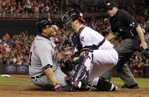Detroit Tigers' Miguel Cabrera, left, is tagged out at home plate by Minnesota Twins catcher Joe Mauer, center, as home plate umpire Ron Kulpa, right, looks on, during the sixth inning of a baseball game, Friday, Sept. 28, 2012, in Minneapolis. (AP Photo/Genevieve Ross)
