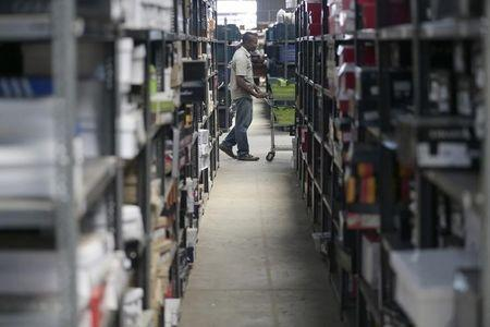 A staff member of on-line retailer Jumia, pushes a cart past shelves at the company's warehouse in Lagos