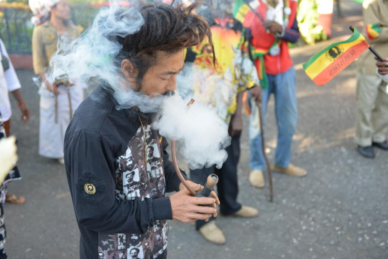 "In this Feb. 6, 2013 photo, a Rastafarian named Bongho Jatusy smokes a pipe of marijuana outside a museum dedicated to the memory of late reggae icon Bob Marley in Kingston, Jamaica. While marijuana is still illegal in Jamaica, where it is known popularly as ""ganja,"" increasingly vocal advocates say that Jamaica could give its struggling economy a boost by taking advantage of the fact the island is nearly as famous for its marijuana as it is for beaches, reggae music and world-beating sprinters. (AP Photo/David McFadden)"