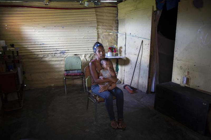 In this photo taken July 25, 2019, Karelys Herrera, 15, holds her baby inside her home during a interview in the Caucaguita neighborhood on the outskirts of Caracas, Venezuela. Herrera said she contemplated suicide after learning she was pregnant at age 14. (AP Photo/Ariana Cubillos)