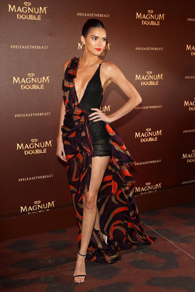 <p>The combination of this asymmetric Versace dress and the slicked back bun ensured Kendall looked every inch the high-fashion model at an event in Cannes. [Photo: Getty] </p>