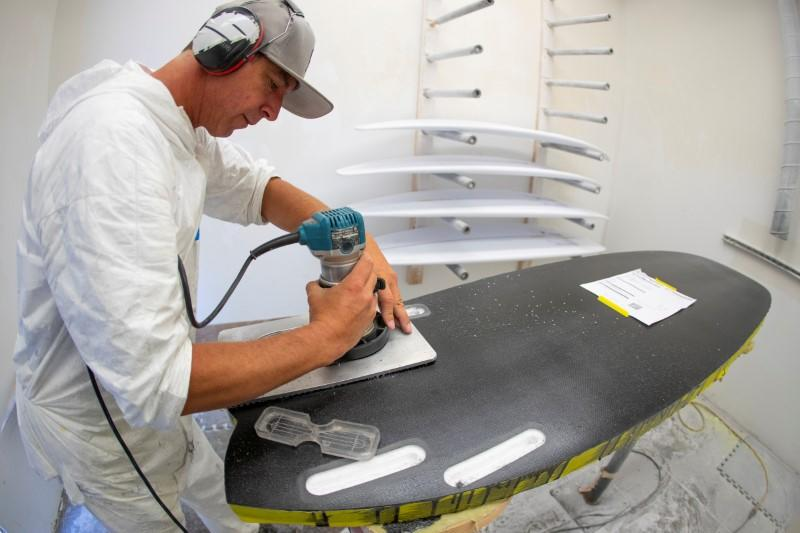 FILE PHOTO: James Black works on a soft INT surfboard at the INT surfboard factory in Carlsbad, California