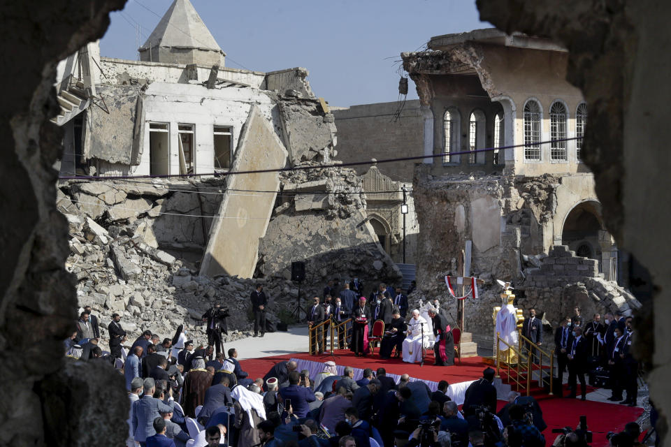 Pope Francis, surrounded by shells of destroyed churches, leads a prayer for the victims of war at Hosh al-Bieaa Church Square, in Mosul, Iraq, once the de-facto capital of IS, Sunday, March 7, 2021. The long 2014-2017 war to drive IS out left ransacked homes and charred or pulverized buildings around the north of Iraq, all sites Francis visited. (AP Photo/Andrew Medichini)