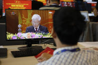 A journalist sitting at the media center watches Nguyen Phu Trong, general secretary of the Communist Party of Vietnam delivering a speech, on screen, during the opening ceremony of the 13th National Congress of Vietnam's Communist Party (VCP), in Hanoi, Vietnam on Tuesday, Jan. 26, 2021. Vietnam's ruling Communist Party has begun a crucial weeklong meeting in the capital Hanoi to set the nation's path for the next five years and appoint the country's top leaders. (AP Photo/Minh Hoang)
