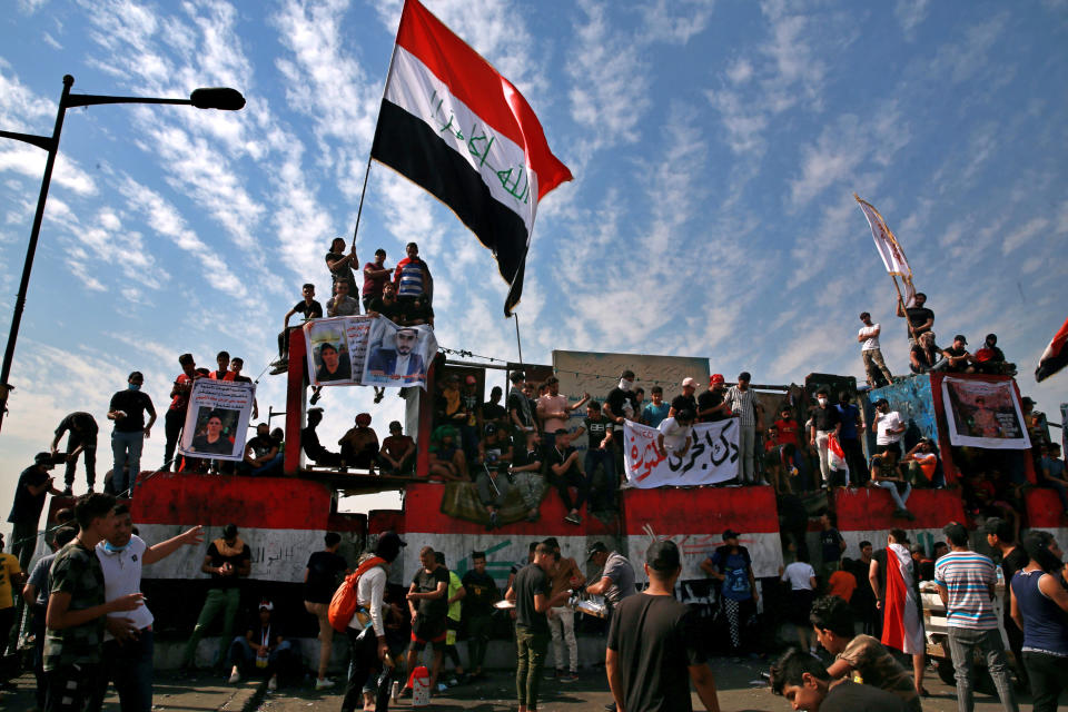 Anti-government protesters gather on the closed Joumhouriya Bridge that leads to the Green Zone government areas in Baghdad, Iraq, Sunday, Oct. 25, 2020. (AP Photo/Khalid Mohammed)