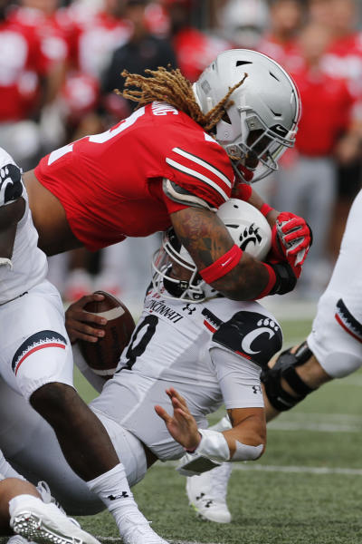 FILE - In this Sept. 7, 2019, file photo, Ohio State defensive end Chase Young, top, sacks Cincinnati quarterback Desmond Ridder during the first half of an NCAA college football game, in Columbus, Ohio. Ohio State said, Wednesday, Nov. 13, 2019, the NCAA has concluded that star DE Chase Young must sit out one more football game before he can return. (AP Photo/Jay LaPrete, File)
