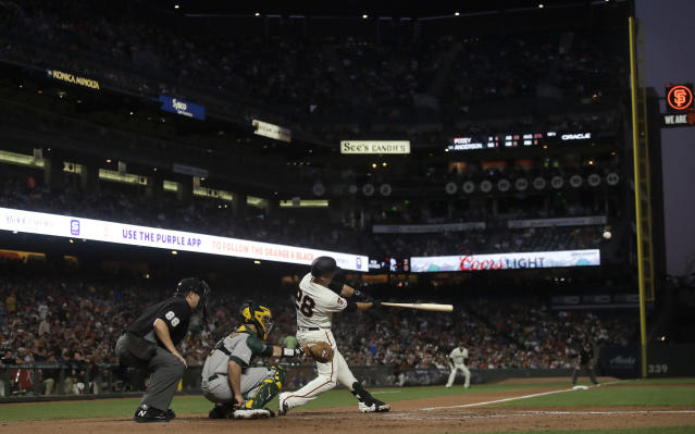 San Francisco Giants' Buster Posey (28) hits a double in front of Oakland Athletics catcher Dustin Garneau during the sixth inning of a baseball game in San Francisco, Tuesday, Aug. 13, 2019. (AP Photo/Jeff Chiu)