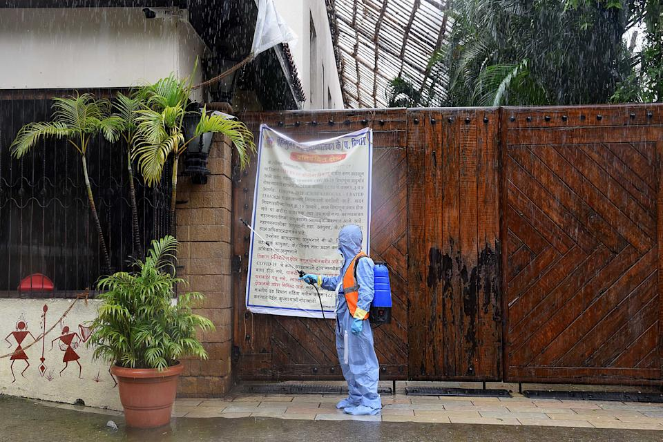 A civic authority worker sprays sanitiser on the main door of the residence of Bollywood star Amitabh Bachchan as he tested positive for COVID-19 in Mumbai on July 12, 2020. - Bollywood megastar Amitabh Bachchan, 77, tested positive for COVID-19 on July 11 and was admitted to hospital in Mumbai, with his actor son Abhishek -- who also announced he had the virus -- saying both cases were mild. (Photo by Sujit Jaiswal / AFP)