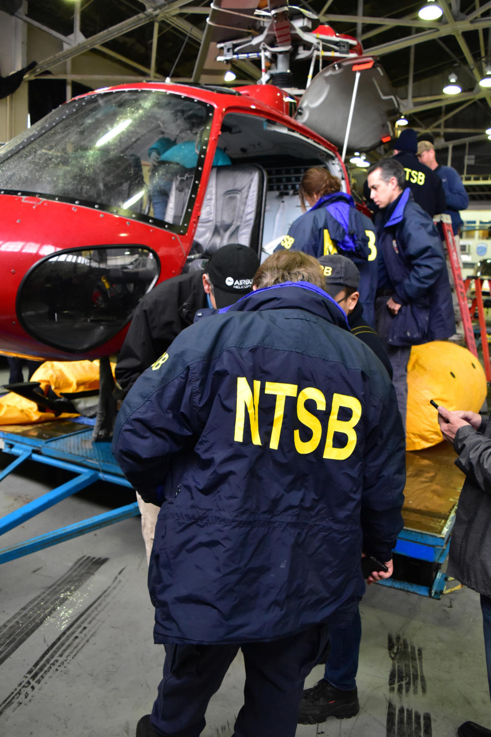 In this March 13, 2018, photo provided by the National Transportation Safety Board, investigators from the NTSB Go Team examine the wreckage of a Liberty Helicopters' helicopter in New York that crashed in the East River on Sunday, March 11. Video from inside the doors-off sightseeing helicopter that crashed in the New York City river last year shows doomed passengers struggling to free themselves from harnesses as the aircraft fills with water. NTSB released transcript of the video on Monday, Sept. 23, 2019. (Chris O'Neil/NTSB via AP)
