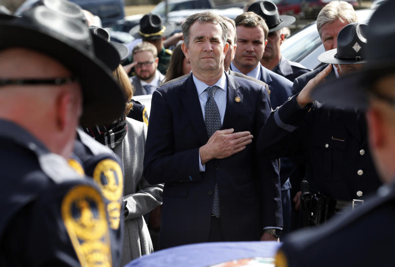 FILE - In this Saturday, Feb. 9, 2019 file photo, Gov. Ralph Northam, left, and his wife, Pam, watch as the casket of fallen Virginia State Trooper Lucas B. Dowell is carried to a vehicle during his funeral in Chilhowie, Va. Two months after his political career was all but dead after the discovery of a controversial photo in his medical school yearbook, life for Northam looks mostly back to normal. (AP Photo/Steve Helber, Pool)