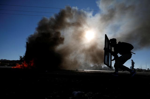 "<p>A Palestinian protester takes cover during clashes with Israeli troops as Palestinians call for a ""day of rage"" in response to President Donald Trump's recognition of Jerusalem as Israel's capital, near the Jewish settlement of Beit El, near the West Bank city of Ramallah, Dec. 8, 2017. (Photo: Mohamad Torokman/Reuters) </p>"
