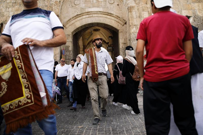A Muslim man carries a prayer mat as he walks near Lions' Gate in Jerusalem's Old City. (Photo: Nir Elias/Reuters)
