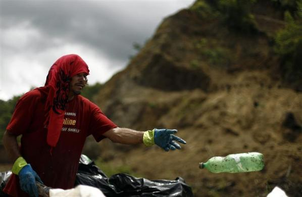 A man collects plastic bottles at a dump site in Garabito, 113 km (70 miles) from San Jose, June 1, 2012. According to the Association Terranostra, Costa Rica produces 4,500 metric tons of garbage every day that ends up on beaches and in the ocean. More than five hundred volunteers participated in the cleaning operation at 25 sites around the country as part of commemorative events for the United Nations' World Environment Day to be marked on June 5.