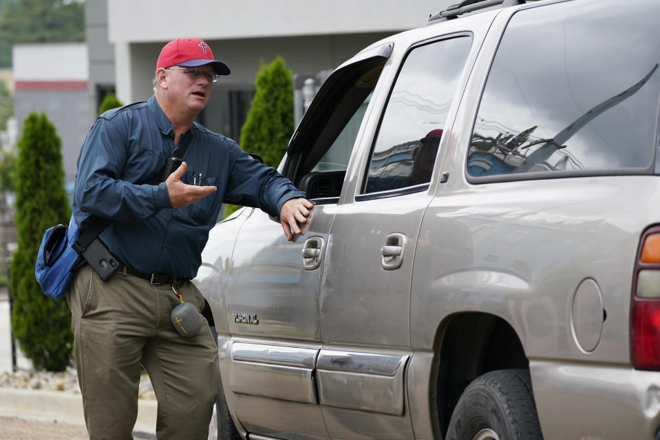 Coleman Boyd, a Mississippi physician an ardent anti-abortion advocate, left, speaks to a driver waiting for a passenger outside the Jackson Women's Health Organization clinic, Thursday, May 20, 2021, in Jackson, Miss. The clinic is Mississippi's only state licensed abortion facility. On May 17, 2021, the U.S. Supreme Court agreed to take up the dispute over a Mississippi ban on abortions after 15 weeks of pregnancy. The issue is the first test of limits on abortion access to go before the conservative majority high court. Their decision could mean more restrictions, and focuses on the landmark 1973 ruling in Roe v. Wade, which established a woman's right to an abortion. (AP Photo/Rogelio V. Solis)