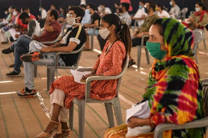 People wait to get inoculated with a dose of the Covishield Covid-19 coronavirus vaccine at Radha Soami Satsang Beas Centre in Amritsar on May 19, 2021.