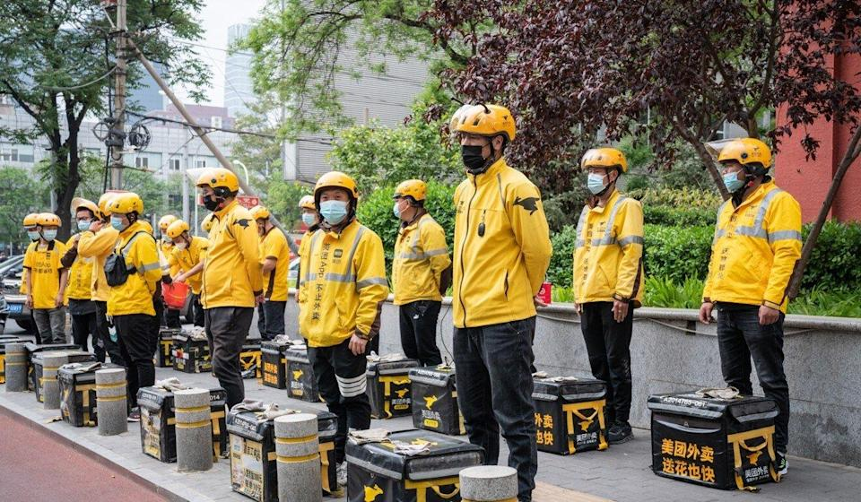 Meituan food delivery couriers stand with their insulated bags during a morning briefing in Beijing on April 21, 2021. Photo: Bloomberg