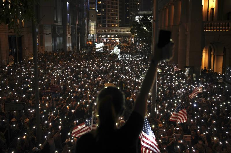 Protestors light their torches during a peaceful rally in central Hong Kong's business district, Monday, Oct. 14, 2019. The protests that started in June over a now-shelved extradition bill have since snowballed into an anti-China campaign amid anger over what many view as Beijing's interference in Hong Kong's autonomy that was granted when the former British colony returned to Chinese rule in 1997. (AP Photo/Felipe Dana)
