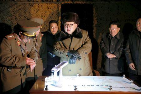 KCNA picture shows North Korean leader Kim Jong Un talking with officials at the ballistic rocket launch drill of the Strategic Force of the Korean People's Army at an unknown location